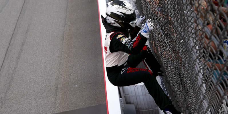 AJ Allmendinger climbs the fence