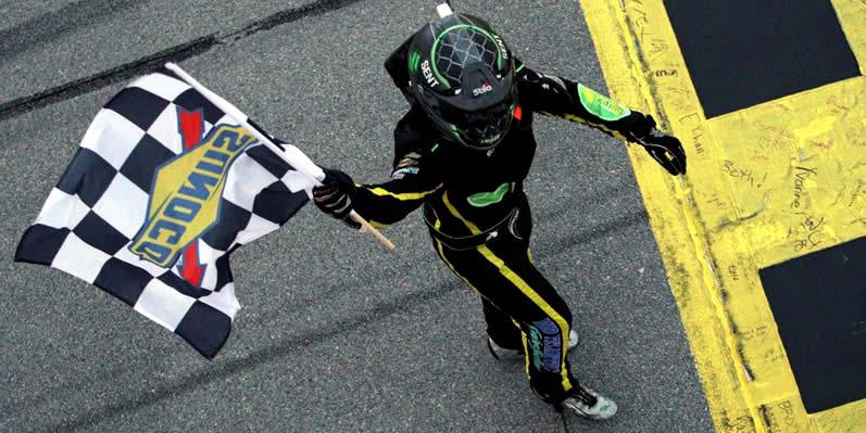 Brandon Brown walks with the checkered flag