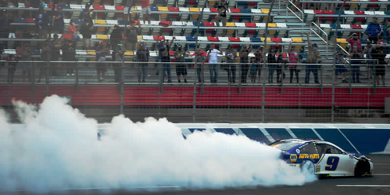 Fans cheer as Chase Elliott celebrates after winning the Bank of America ROVAL 400 at Charlotte Motor Speedway