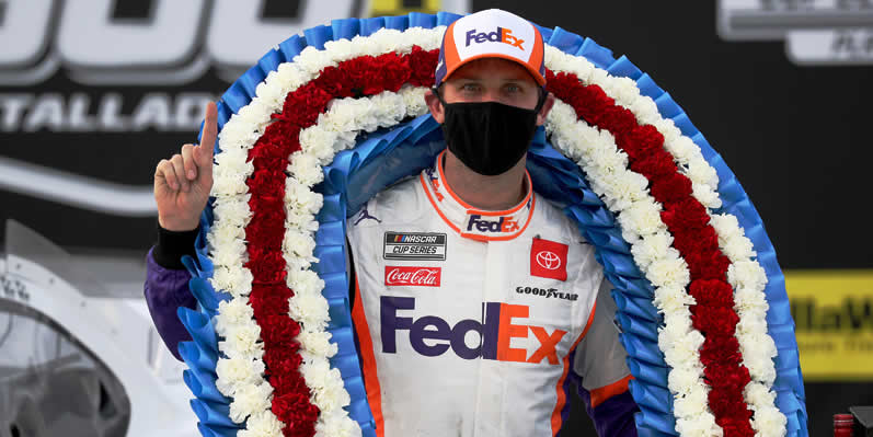 Denny Hamlin celebrates in Victory Lane after winning the YellaWood 500 at Talladega Superspeedway