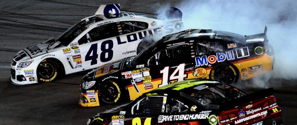 Jimmie Johnson, driver of the #48 Lowe's Dover White Chevrolet, and Tony Stewart, driver of the #14 Rush Truck Centers/Mobil 1 Chevrolet, spin after an on track incident during the NASCAR Sprint Cup Series Toyota Owners 400 at Richmond International Raceway