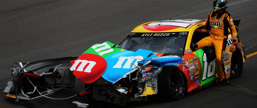 Kyle Busch climbs from his tore up race car at Kansas Speedway